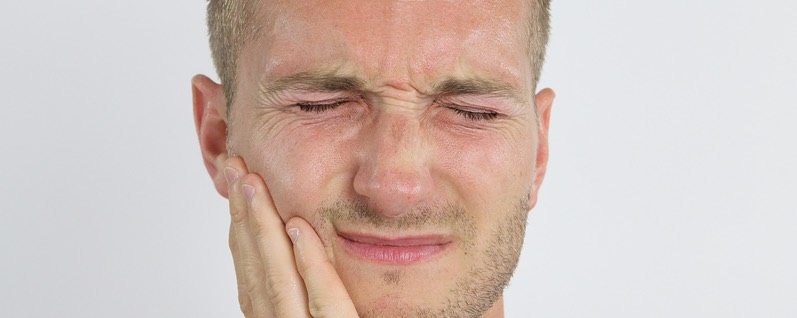 man with tooth pain, grimacing